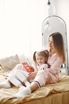 Matka i córka, ciesząc się na łóżku. trzymając czerwone pudełko. dzień matki.