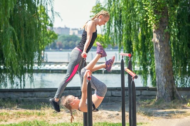 Matka i córka ćwiczą sprzęt fitness w parku