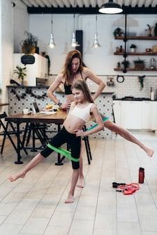Matka i córka ćwiczą w domu robiąc wyciąganie nóg na bok z opaską oporową.