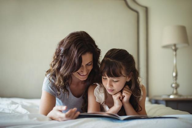 Matka i córka czyta książkę podczas gdy kłamający na łóżku