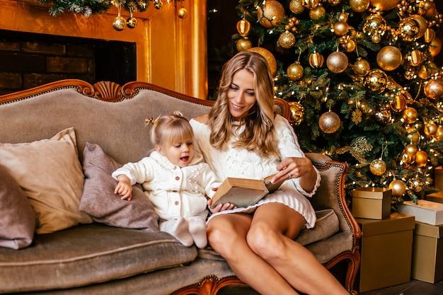 Matka i córka czyta książkę przy kominkiem w wigilię bożego narodzenia. urządzony salon z drzewem, kominkiem i prezentami. zimowy wieczór w domu dla rodziców i dzieci.