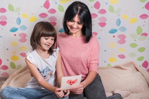 Matka i córka czyta małego kartka z pozdrowieniami na łóżku