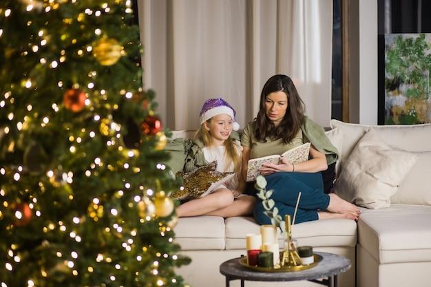 Matka i córka czytają książkę z włączonymi światłami choinki