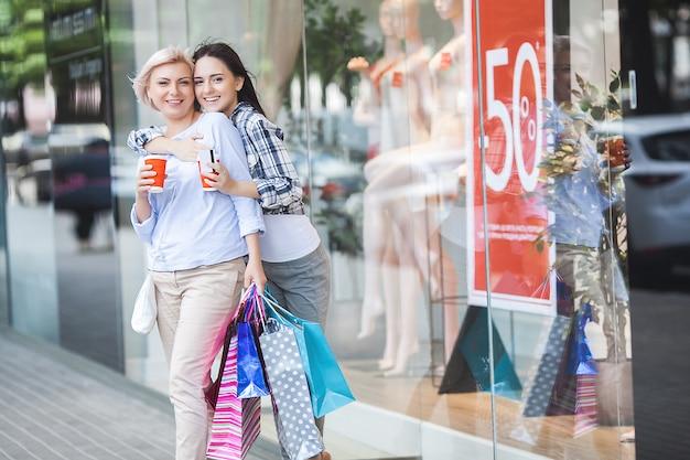 Matka i córka dorosły robi zakupy razem. w połowie dorosła mama i jej córka w centrum handlowym.