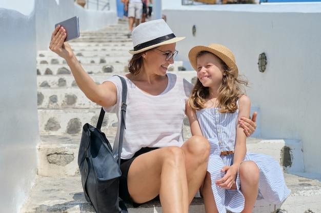 Matka i córka dziecko biorąc selfie na smartfonie siedząc na białych schodach santorini