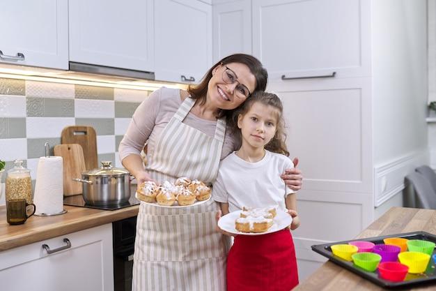 Matka i córka dziecko razem w domu kuchnia ze świeżo upieczonymi babeczkami. zdjęcie do domowego albumu, rodziny, dnia matki, domowego pieczenia zdrowej żywności