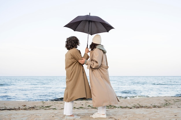 Matka i córka dzielą czułą chwilę na plaży pod parasolem