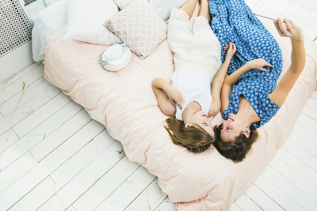 Matka i córka dziewczyna robi selfie na telefon komórkowy szczęśliwe i piękne domy w sypialni na łóżku