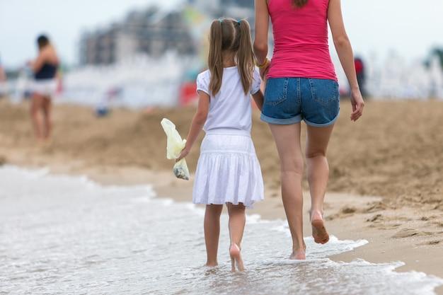 Matka i córka dziewczynka idzie razem na piaszczystej plaży w wodzie morskiej w lecie z bosymi stopami w ciepłe fale oceanu.