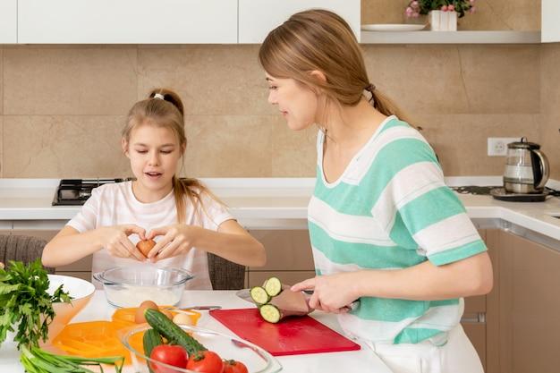 Matka i córka gotujemy w domu. robienie ciastek, wnętrze kuchni, pojęcie zdrowej żywności. wesołe dziecko.