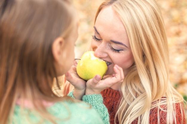 Matka i córka je jabłka w jesień parku.