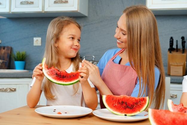 Matka i córka jedzenie arbuza w domu