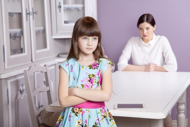 Matka i córka kłócą się z powodu nadużywania telefonu typu tablet. problem społeczny między rodzicami a dziećmi. ujęcie studyjne...