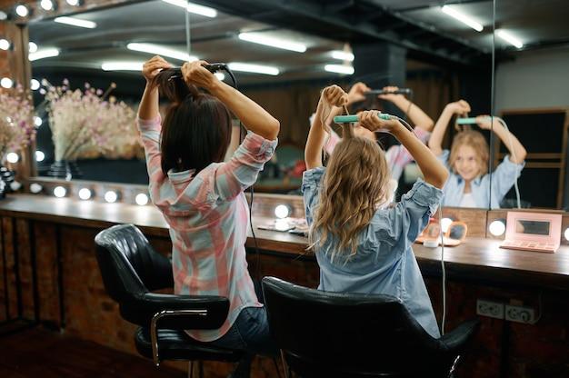 Matka i córka kręcą fryzury w salonie fryzjerskim