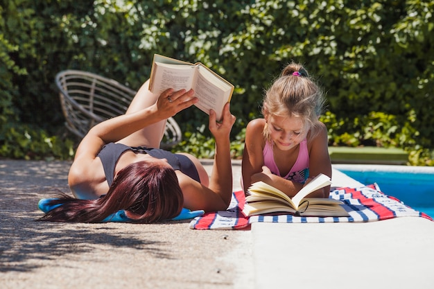 Matka i córka leżącego przy basenie czytania