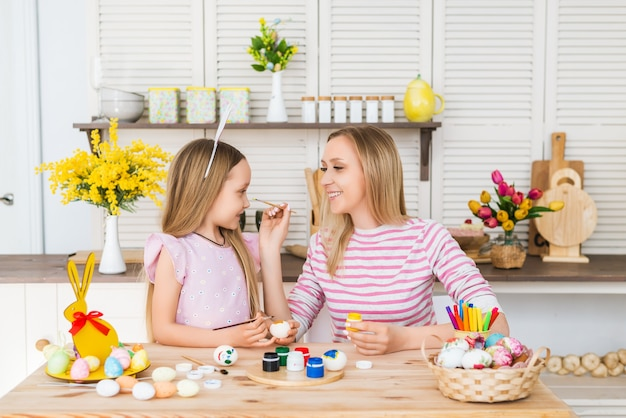 Matka i córka malują jajka. szczęśliwa rodzina przygotowuje się do wielkanocy. cute little girl dziecko sobie uszy królika.