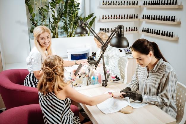 Matka i córka. matka i córka ubrana w czarno-białe ubrania, odwiedzając salon manicure