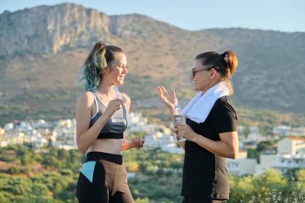 Matka i córka mówi i pije wodę po treningu