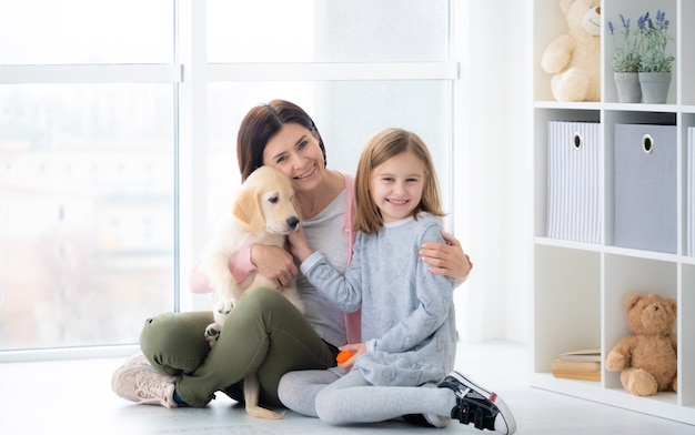 Matka i córka obejmując psa