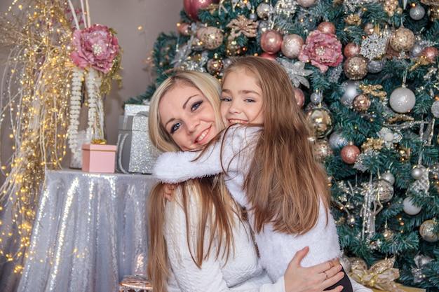 Matka i córka obok choinki. świąteczny nowy rok i boże narodzenie. piękna mama i córka.