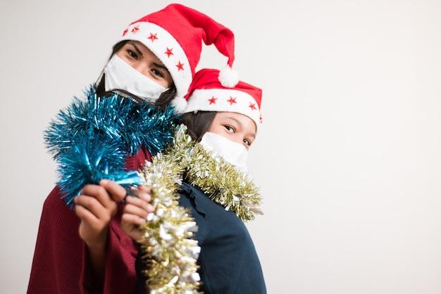 Matka i córka patrząc do kamery w kapeluszu świętego mikołaja i masce chirurgicznej trzymającej świecidełko błyszczały na białym tle.