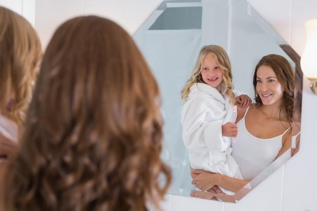 Matka i córka patrzeje łazienki lustro