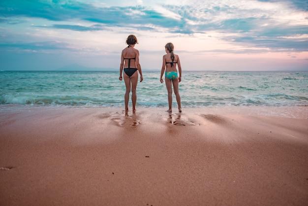 Matka i córka patrzeje zmierzch przy plażą