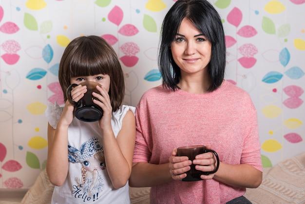 Matka i córka pije herbatę z kubków