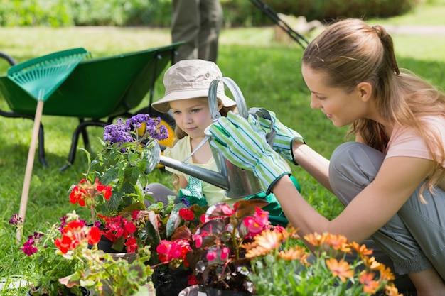 Matka i córka podlewania roślin w ogrodzie