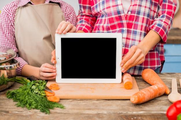 Matka i córka pokazuje pustego ekranu cyfrową pastylkę na ciapanie desce z warzywami