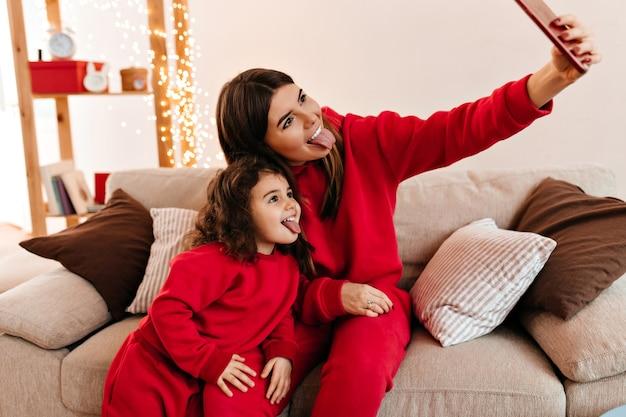 Matka i córka pozują z wyciągniętymi językami. stylowa mama robi selfie z dzieckiem w domu.