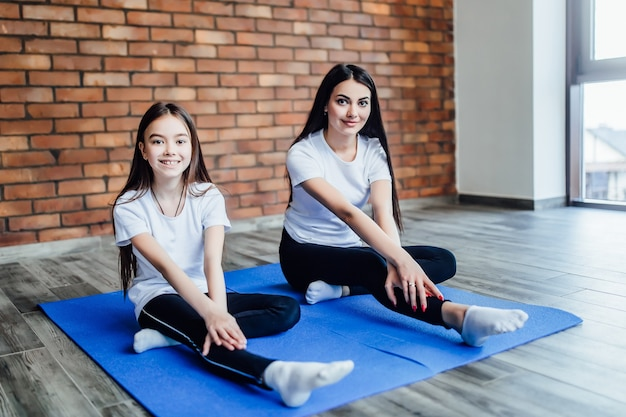 Matka i córka praktykowania jogi w pozie motyla w domu... zdrowie.