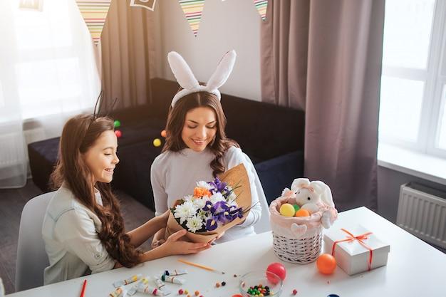 Matka i córka przygotowują się do wielkanocy. dziewczyna daje mamie piękny bukiet. wielkanocne dekoracje słodyczy i farby na stole.