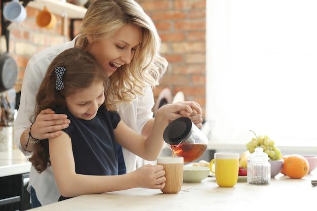 Matka i córka przygotowuje filiżankę herbaty