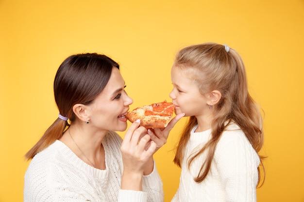 Matka i córka razem jeść pizzę i bawić się na białym tle nad żółtym studio