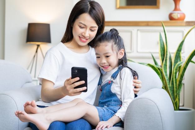 Matka i córka razem oglądają wideo na telefonie w domu