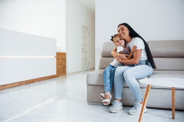 Matka i córka razem siedzą na kanapie w poczekalni kliniki.