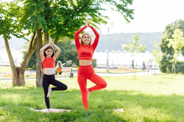 Matka i córka robi ćwiczenia jogi na trawie w parku w ciągu dnia
