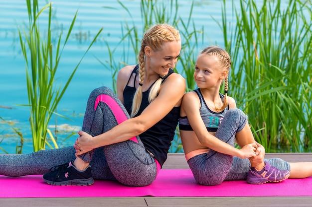 Matka i córka robi ćwiczenia na siłowni na trawie przy molo nad rzeką
