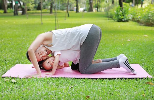 Matka i córka robi ćwiczeniu w ogródzie