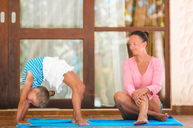 Matka i córka robi joga ćwiczeniu outdoors