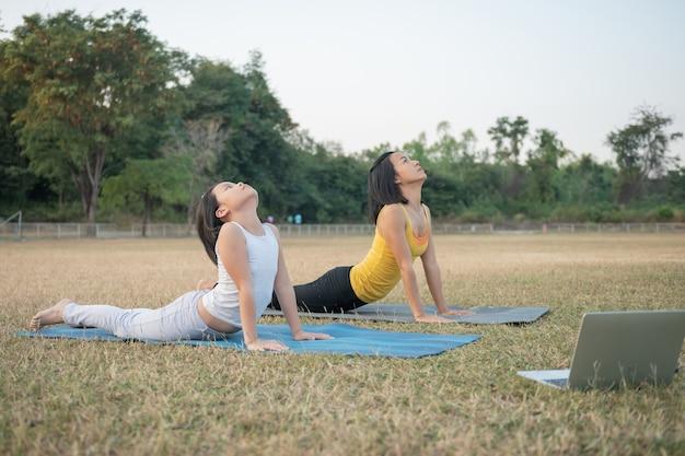 Matka i córka robi joga. kobieta i dziecko w parku. sporty na świeżym powietrzu. zdrowy sportowy styl życia, oglądanie ćwiczeń jogi samouczek wideo online i rozciąganie klatki piersiowej i kręgosłupa.