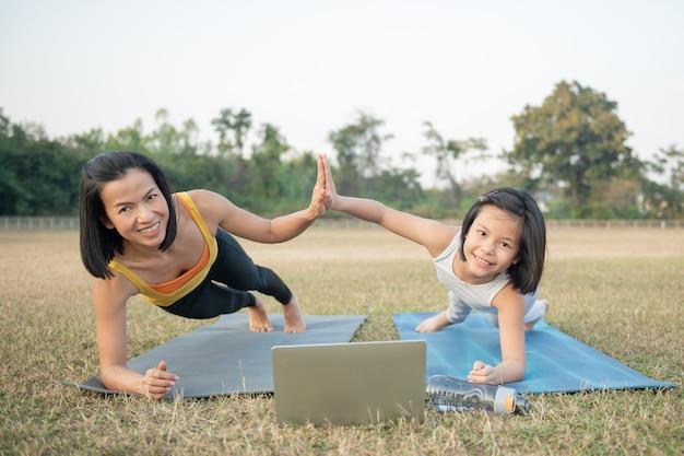 Matka i córka robi joga. kobieta i dziecko w parku. sporty na świeżym powietrzu. zdrowy sportowy styl życia, poza chaturanga. dobre samopoczucie, koncepcja uważności, oglądanie samouczka wideo online na laptopie