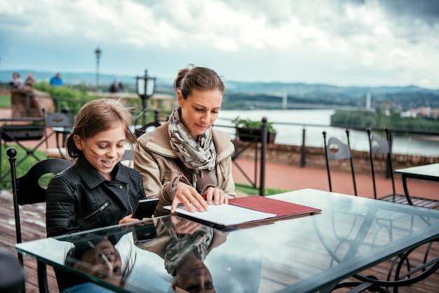 Matka i córka robi rozkazowi w kawiarni