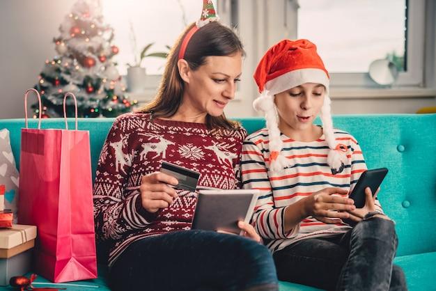 Matka i córka robi zakupy online w domu podczas bożych narodzeń