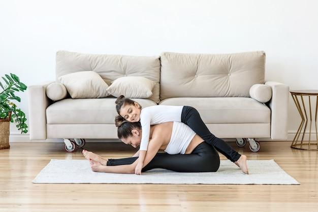 Matka i córka robią jogę w domu
