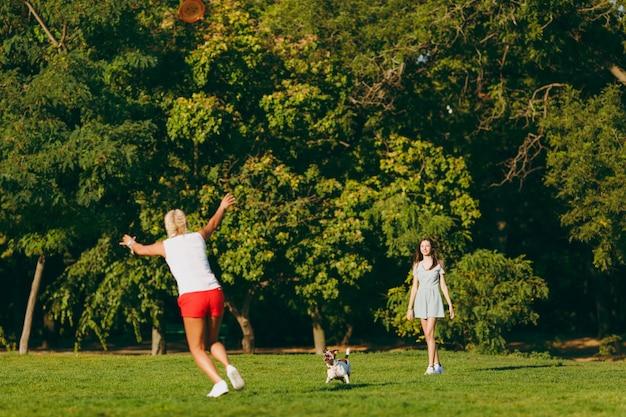Matka i córka rzucają pomarańczowy latający dysk małemu zabawnemu psu, który łapie go na zielonej trawie. mały jack russel terrier zwierzak gra na świeżym powietrzu w parku. pies i kobiety. rodzina odpoczywa na świeżym powietrzu