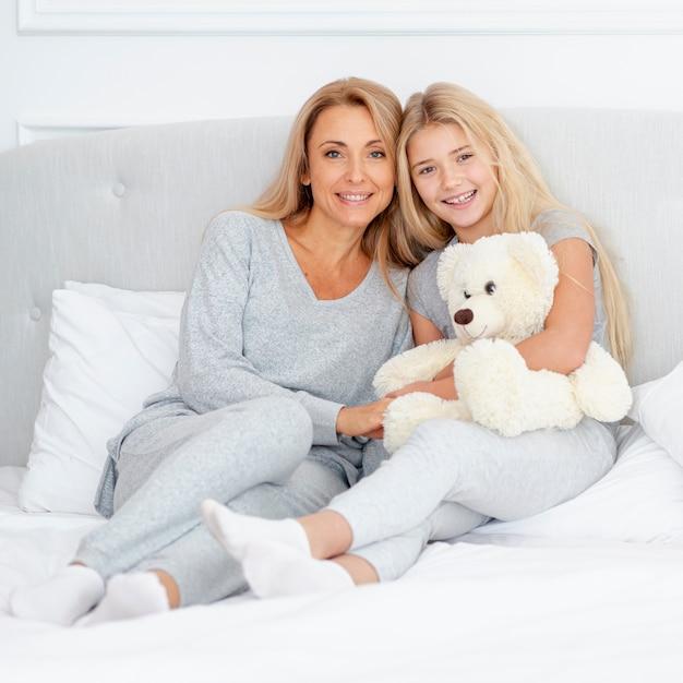 Matka i córka siedzi na łóżku