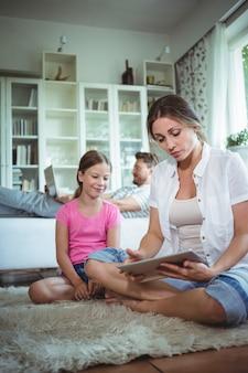 Matka i córka siedzi na podłodze i przy użyciu cyfrowego tabletu
