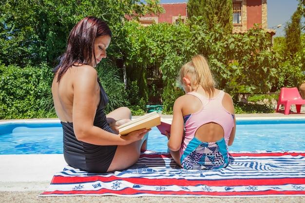 Matka i córka siedzi przy basenie z książkami